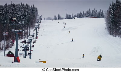 Ski lifts work on a snowy mountainside Timelapse - People...