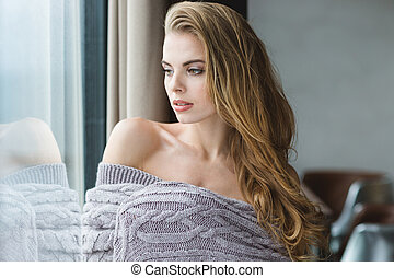 Portrait of seductive blonde female wrapped in grey knitted...