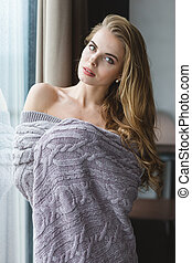 Beautiful tempting young woman with long hair in knitted...