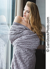 Attractive alluring female in grey coverlet looking through...