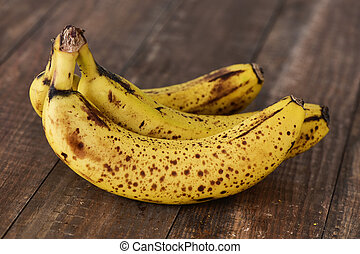 bananas on a wooden surface - closeup of a bunch of ripe...