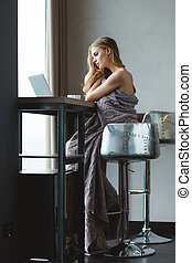 Beautiful pensive woman wrapped in grey knitted coverlet...