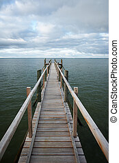 Footbridge under moody sky - Pier over green water and under...