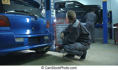 Checking exhaust with device - Mechanic checking exhaust...