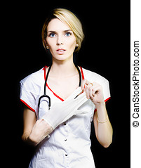 Serious young nurse removing her latex gloves - Serious...