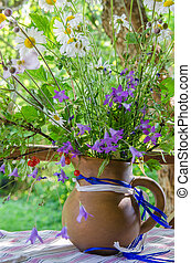 Jug with a bouquet of summer flowers on a table in the garden