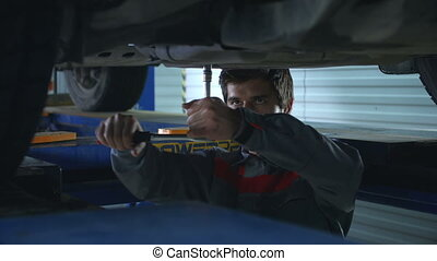 Twisting the screws - Mechanic twisting the screws under the...