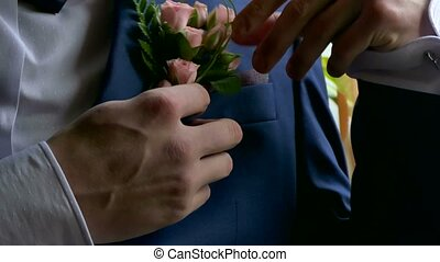 groom boutonniere on man corrects his pocket hand - groom...