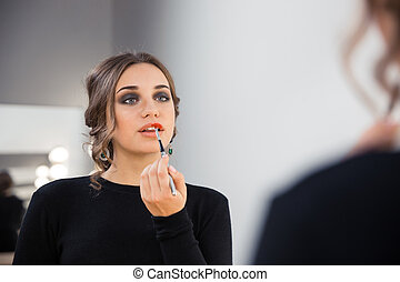 Attractive woman applying lipstick on her lips