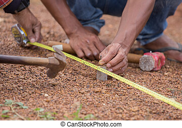Worker working with measuring tape, hammer and nail