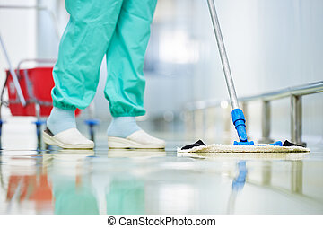 worker cleaning floor with mop - Floor care and cleaning...