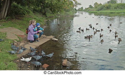 Mother and his little son feeding ducks at autumn