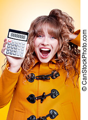 Excited winter woman holding savings calculator - Excited...