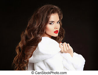 Beautiful Fashion Girl in White Mink Fur Coat. Makeup. Winter portrait. Beauty woman model with elegant long hair style posing isolated on black studio background.