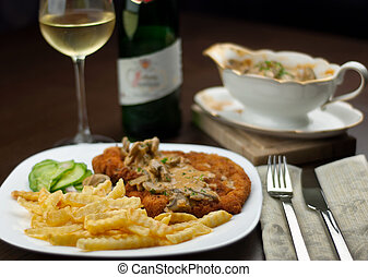 Schnitzel, french fries, cucumber salat and white wine with...