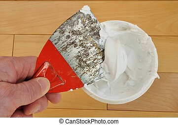 Putty Knife with Spackling Paste on a Wood Floor