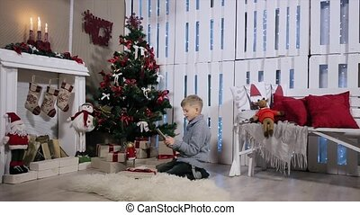 Young boy To speak through digital tablet, white Room with Fireplace and Christmas Tree