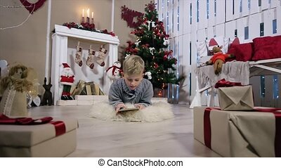 The boy chooses a gift for the digital tablet, the camera moves to a boy, white Room with Fireplace and Christmas Tree