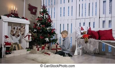 A boy sitting near Christmas tree, turns the smartphone in...
