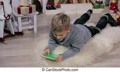 Little boy lying on the floor, use digital display, white...