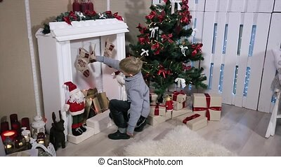 A boy looking gifts toes by the fireplace, white Room with Fireplace and Christmas Tree. Wide angle