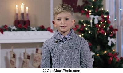 Little boy holding up two fingers, smiling, look at camera, white Room with Fireplace and Christmas Tree, Medium