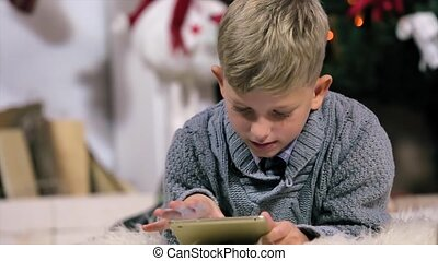 Little boy lying on the ground and played with a digital tablet, The camera moves from the boy and then the boy, white Room with Fireplace and Christmas Tree, Close Up, people