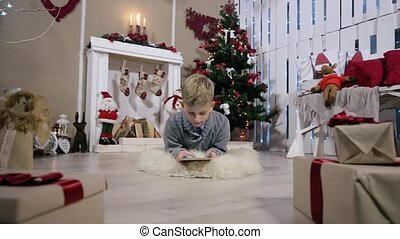 Little boy lying on the ground and played with a digital tablet, The camera moves from the boy and then the boy, white Room with Fireplace and Christmas Tree