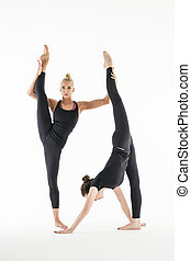 Two girls stretch - Two flexible girl in a black leggings...