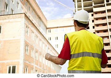 Building Inspector Reviewing Blueprints - construction site...