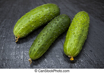 Fresh appetizing tasty cucumber on a stone background -...