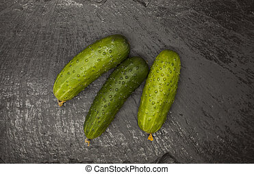 Fresh appetizing tasty cucumber on a stone background. -...