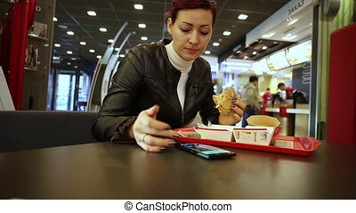 Woman eating burger and using smartphone - Woman sitting in...