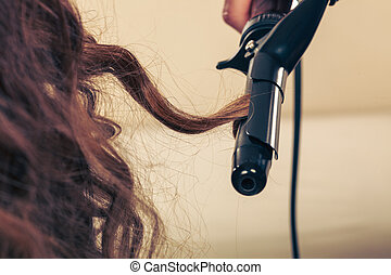 Stylist curling hair for young woman. Girl care about her...