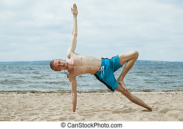 Man doing yoga on the beach