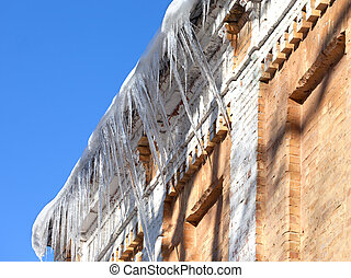 Snow-covered roof of old house with icicles in sun winter...