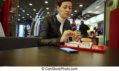 Woman eating burger and looking smartphone - Woman sitting...