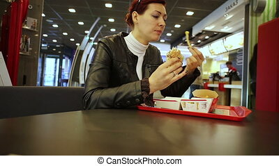 Young woman eating burger in fast food restaurant