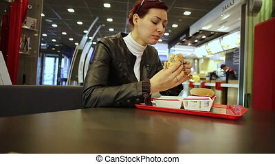 Woman eating burger in a fast food restaurant - Woman...