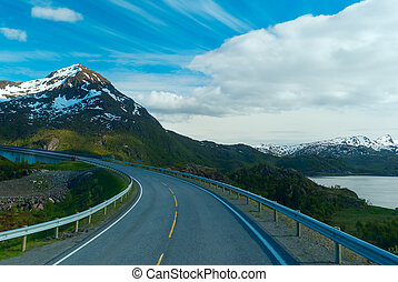 Asphalt road to Norvegian mountains in sunny summer day