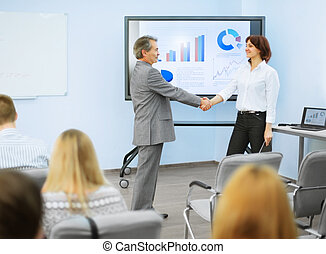 successful presentation - business partners shake hands...
