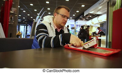 Man eating burger in a fast food restaurant - Man sitting in...