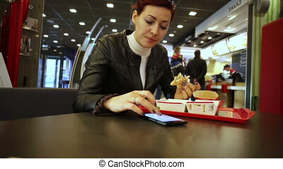 Young woman eating burger and using smartphone