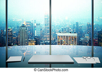Modern office with glassy table, laptop and night megapolis...