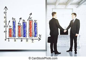 Businessmen shake hands in loft office with white wall with...