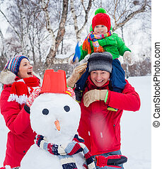 Family with a snowman - Portrait of Happy family of three...