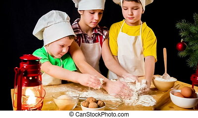 Three kids kneading the douhg together