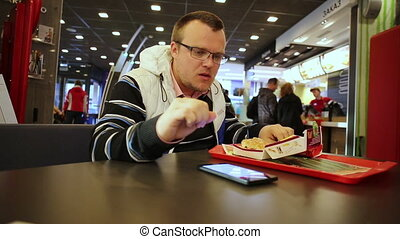 Young man eating burger and using smartphone - Man sitting...