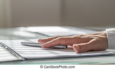Male hand lying on a contract or document and a pen...