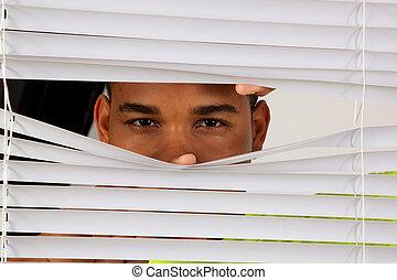 Black man looking through blinds - Black man peeking though...